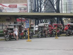 Filipino tricycles parked at a Manila terminal, awaiting fares.