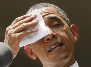 U.S. President Obama wipes his brow while he speaks about his vision to reduce carbon pollution in Washington