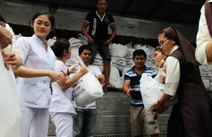 Picture 2 - Ecumenical Effort: Roman Catholic Religious Sisters, Nurses, Protestant and Roman Catholic volunteers line up at the compound of the National Council of Churches in the Philippines to pass relief goods to load a truck headed for the survivors of typhoon Yolanda . (Photo: ACT/Sandra Cox)