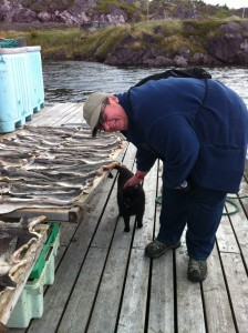 Sara Stratton petting a black cat at a fish flake in Southport, Trinity Bay, Newfoundland.