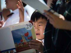 Jason Tian, 7, from China, reads along with the French language portion while taking the oath of citizenship with his brother and mom during a special Canada Day citizenship ceremony in West Vancouver, B.C., on Saturday, July 1, 2017. DARRYL DYCK / THE CANADIAN PRESS