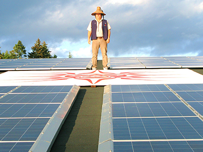 Chief Standing on Solar roof. Photo by Andrew Moore.