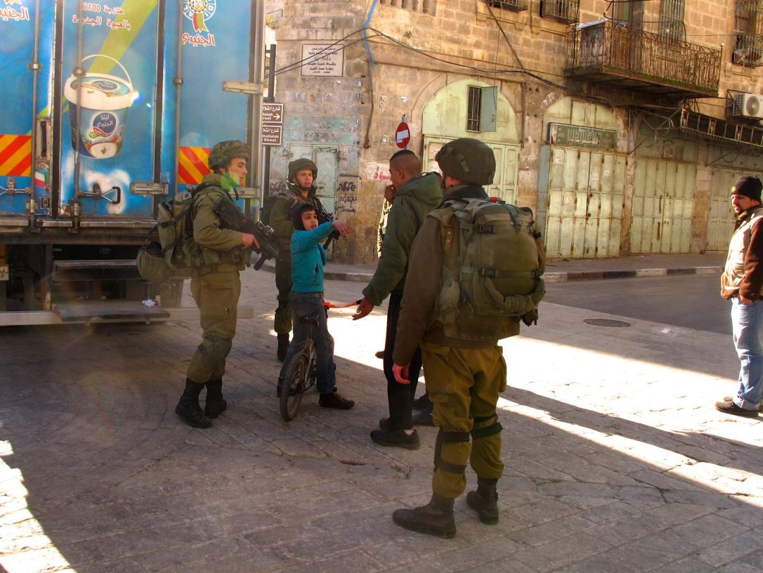 Group of soldiers surrounding boy in Hebron. Photo by Mia Haglund