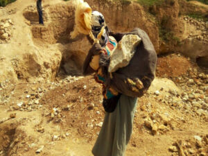 woman carrying rocks from coltan mine